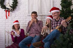 Joyful holiday in the family - parents and teens children, in a. Santa hats, are having fun and expressive singing in front of a Christmas tree, in anticipation Stock Photos