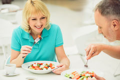 Joyful husband and wife entertaining in restaurant. Happy mature married couple is enjoying fresh salad in cafe. Woman is sitting at table and laughing Stock Photos