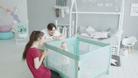 Parents having fun with baby standing in playpen stock footage