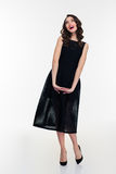 Joyful inspired retro styled woman in black dress and  shoes Royalty Free Stock Image