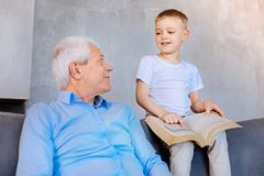 Joyful intelligent boy pointing at the book page. Explain me. Joyful intelligent curious boy holding a book and pointing at its page while asking his grandfather Stock Photo