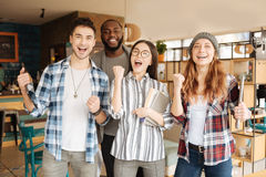 Joyful international students expressing emotions. Yes we did. Happy group of international students are standing and emotionally showing excitement Royalty Free Stock Photos