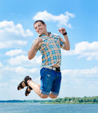 Joyful jump at summer. The young man, against the blue sky, jumps in height Royalty Free Stock Images