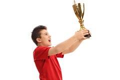 Joyful junior athlete lifting a trophy Stock Photo