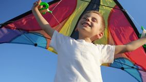 Joyful kid boy playing with bright toy kite against summer blue sky background. Childhood. Fantasy, imagination concept.  stock video footage