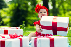 Joyful kid girl with colorful gift boxes Stock Images