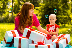 Joyful kid girl and mother with gift boxes Royalty Free Stock Photos