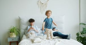 Joyful kid jumping on bed while mother using smartphone father holding tablet stock footage