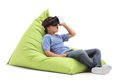 Joyful kid looking in a VR goggles. Seated on a comfortable green beanbag isolated on white background Stock Photography