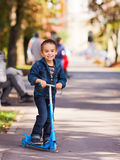 Joyful kid riding a scooter. Joyful little boy with kick scooter playing outdoors Royalty Free Stock Photography