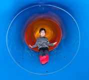 Joyful kid sliding in tube slide Stock Images