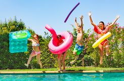 Joyful kids having fun during summer pool party. Portrait of age-diverse boys and girls with inflatable swim toys jumping into the water, having fun during stock image