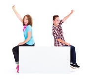 Joyful Kids sitting on Empty Billboard. Excited kids cheering while sitting on blank billboard royalty free stock photos