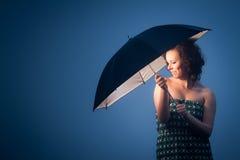 Joyful kvinna som skyddas av ett paraply Arkivbild