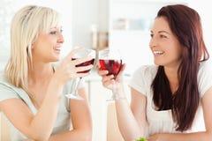 Joyful kvinnor som rostar med wine Fotografering för Bildbyråer