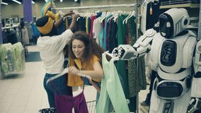 Joyful ladies are picking clothes with a cyborg near them. 4K