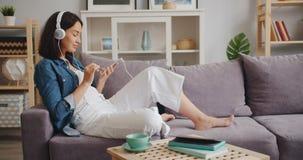 Joyful lady enjoying music in headphones touching smartphone screen at home stock footage