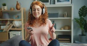 Joyful lady enjoying music in headphones using smartphone dancing on bed. Joyful young lady is enjoying music in headphones using smartphone dancing sitting on stock video
