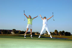 Joyful lady Golfers. Two senior women jump for joy on the golf course Stock Images