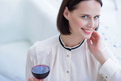 Joyful lady relaxing in restaurant. Confident young woman is drinking wine and smiling. She is sitting and looking at camera flirtingly Royalty Free Stock Photo