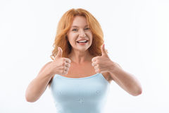 Joyful lady showing ok sign. Everything is okay. Happy red-haired woman is giving thumbs up and smiling. She is standing and looking at camera with joy. Isolated Stock Images