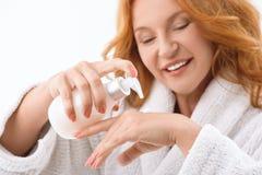 Joyful lady squeezing moisturizer on hand Stock Images