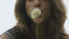Joyful lady trying to blow at dandelion but it stays intact, funny woman attempt. Stock footage stock video