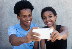 Joyful laughing african american couple taking selfie with phone stock images