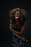 Joyful laughing African American woman against a dark background Stock Image