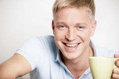 Joyful laughing young man enjoying a cup of coffee. Royalty Free Stock Photo