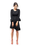 Joyful laughing young woman in black dress looking down with windy flying clothes Stock Images