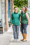 Joyful lesbian couple standing outdoors royalty free stock images