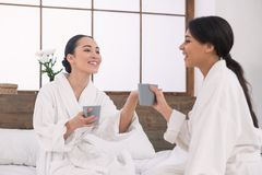 Joyful lesbian women having tea. Romantic day. Joyful lesbian women having tea together while spending a day in the spa Royalty Free Stock Images