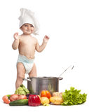 Joyful little boy in chef's hat. Playing with casserole and vegetables Royalty Free Stock Photos