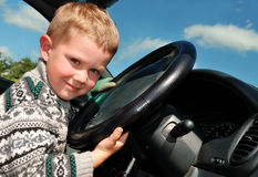 Joyful little boy at driver position in a car Stock Photography