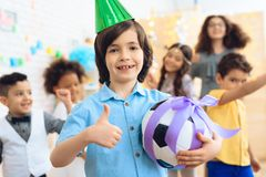 Joyful little boy in green festive cap holds soccer ball in ribbon and shows thumbs up. stock photo