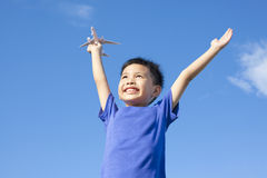 Joyful little boy holding a toy with blue sky. Background Royalty Free Stock Images