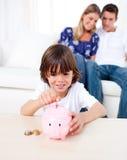 Joyful little boy inserting coin in a piggybank Stock Images