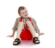 Joyful little boy in a plaid shirt, red shorts and. Flip-flops sitting on the floor spreading their arms - isolated on white background Stock Photo