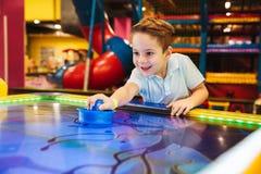 Joyful little boy playing air hockey. At Arcade centre Royalty Free Stock Image