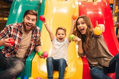 Joyful little boy playing on a slide with his parents. At entertainment centre stock photos