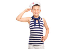 Joyful little boy in a sailor uniform saluting. Towards the camera and smiling isolated on white background Royalty Free Stock Photo