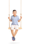 Joyful little boy sitting on a swing Stock Photo