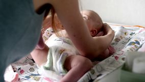 Joyful little child lies on a changing table. And waving his arms and legs stock video