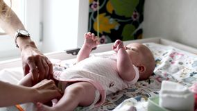 Joyful little child lies on a changing table. And waving his arms and legs stock footage