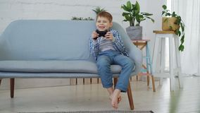 Joyful little child playing videogame alone having fun sitting on couch at home. Modern technologies, happy childhood. Joyful little child is playing videogame stock footage