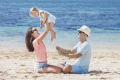 Joyful little family having fun together on the beach. Portrait of joyful little family having fun together on the beach Royalty Free Stock Photo