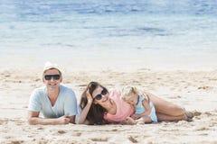 Joyful little family having fun together on the beach. Portrait of joyful little family having fun together on the beach Stock Photo