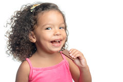 Joyful little girl with an afro hairstyle eating a chocolate bar Royalty Free Stock Images