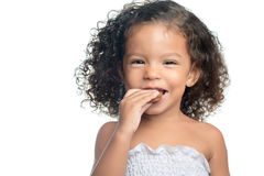 Joyful little girl with an afro hairstyle eating a chocolate cookie. Isolated on white Royalty Free Stock Image